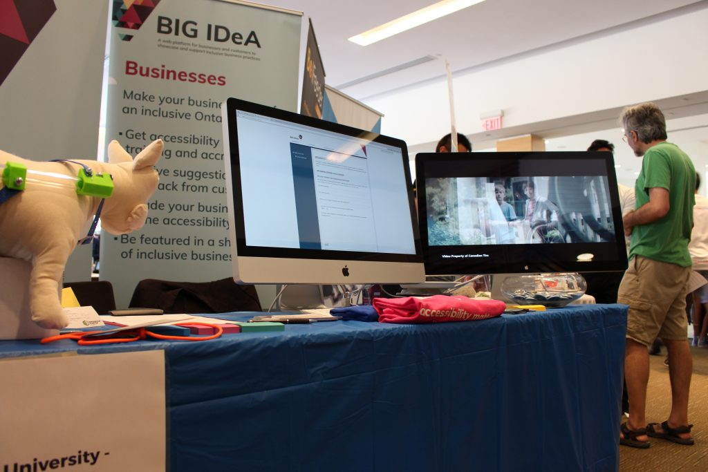 Photo of the BIG IDeA display booth at the 2017 Maker Festival. Two large screens showcasing the BIG IDeA website and video.