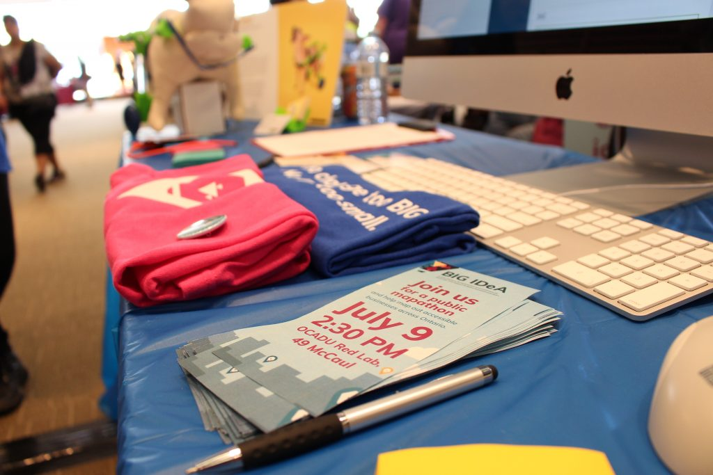 Photo of the BIG IDeA display booth at the 2017 Maker Festival. Table with bright pink and blue team shirts, and brochures on it.