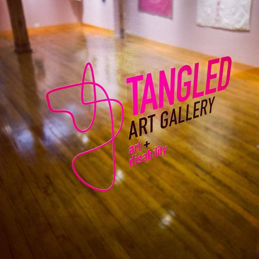 """Image is a photograph of the gallery logo and name """"Tangled Art Gallery art + disability"""" pasted on the glass doors of the gallery. Seen beyond the logo is the actual gallery space showing an open space, as well as art hung on the wall at a lower height than what is seen in most other galleries. This is done to accommodate people in a seated position."""