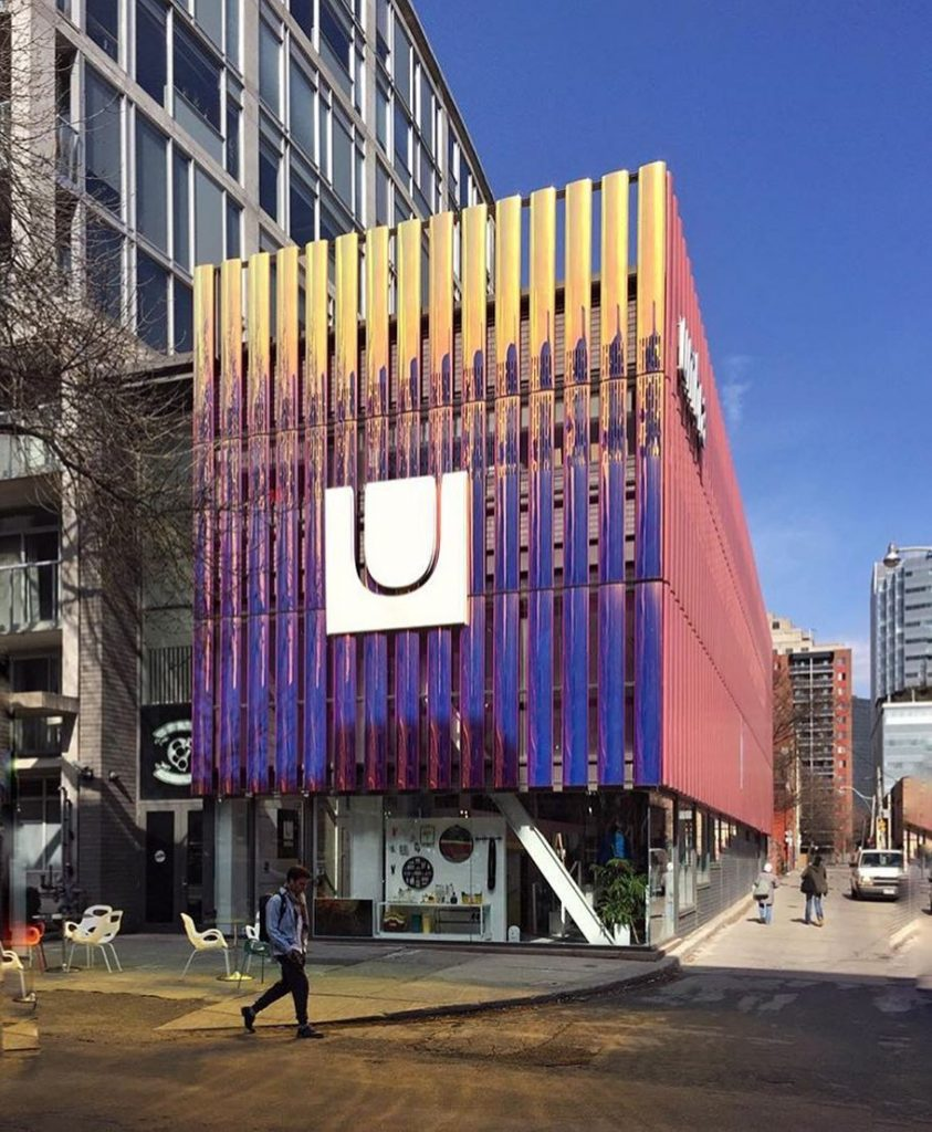 This image is a photograph of the outside of the Umbra building taken during the daytime and includes the chairs outside that can be used by the community.