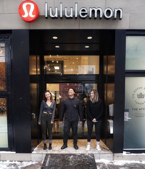 This image is a photograph of the entrance of the Lululemon store and includes three people smiling standing on the front step and the stopgap.ca ramp.