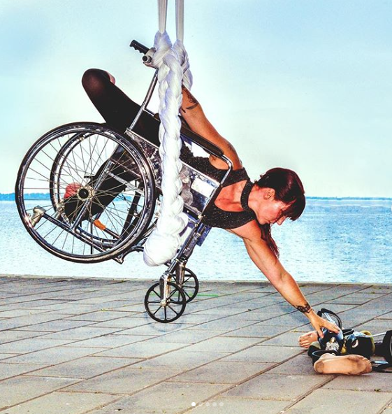 This image is a photograph of a dancer using a wheelchair, both are suspended from a braided rope one foot off the ground reaching for her prosthetic legs on the ground.