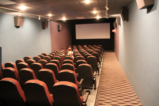 Image is of a photograph of one of the movie theatres and shows the ramp going down to the front of the theatre and seats located to the left of the ramp.