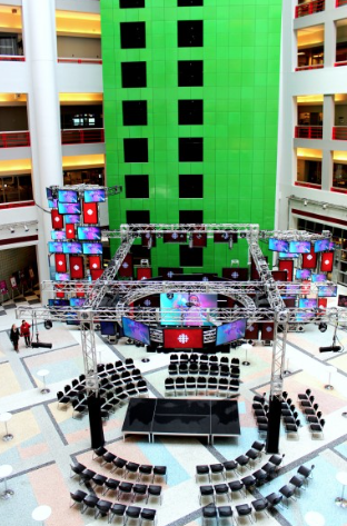 Shows a view of the Barbara Forum Atrium looking down from the 3rd floor. Showing a large open space with seating around a temporary stage.
