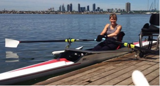 This image is a photograph of a person sitting in a rowing scull next to a dock. On the dock is their empty wheelchair.