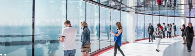 This image is of a photograph that shows a wall of glass that stretches from floor to ceiling, with people standing around looking out. Out the windows, you can see some of Toronto Island and Lake Ontario.