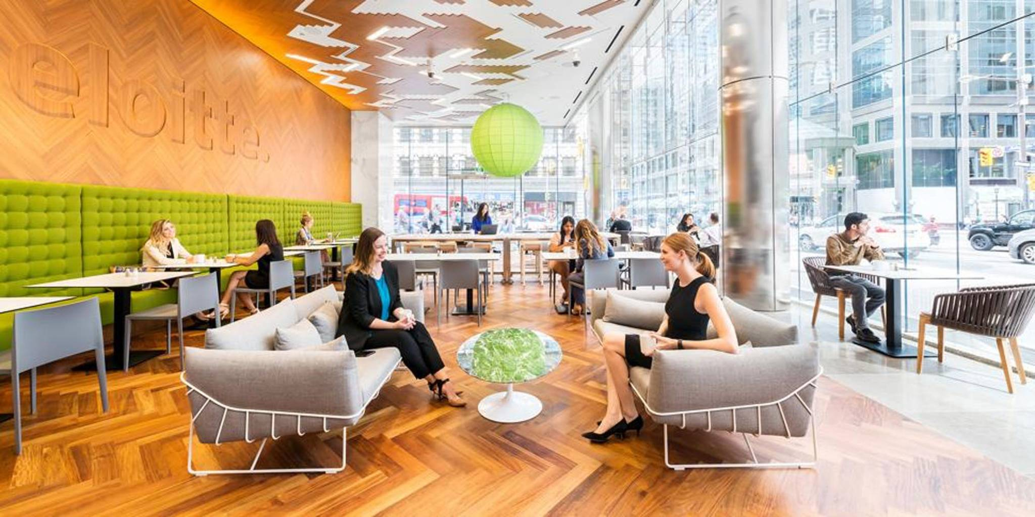 This image is a photograph of the inside of the Deloitte building in a cafe style room and includes people sitting down some of whom are socializing.