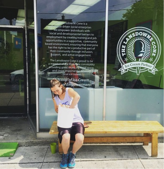 "This image is of a photograph that shows someone sitting on a bench outside the Lansdowne Scoop, scooping ice cream from a very large bucket. Visible in the photo is a small green ramp from Stopgap.ca. Also visible on the storefront glass is a message from the store that reads: ""The Lansdowne Cone is a purpose-driven social enterprise. We empower individuals with social and developmental barriers to employment by creating training and job opportunities in a supportive, community-based environment; ensuring that everyone has the right to be a productive part of their community through inclusion, support and active engagement. The Lansdowne Cone is proud to be a member of the Bloordale community providing good times, inclusive space and (most importantly) fabulous local ice cream! A Scoop of Ice Cream, and a Heap of Empowerment."""