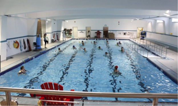 This image is of a photograph that shows an indoor swimming pool, with ramp access into the water.