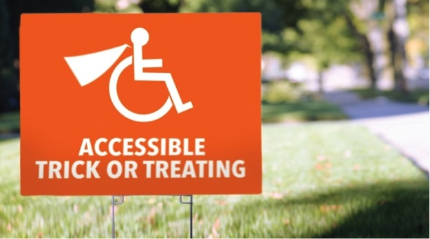 This image is of a photograph that shows an orange coloured sign planted on a lawn of grass. The sign features an image of the international symbol of access with a superhero cape added to the design.