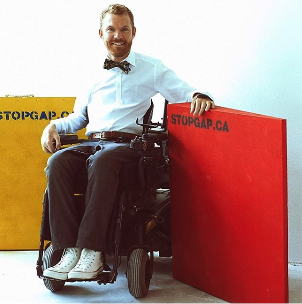 This image is a photograph of Luke Anderson, using a power wheelchair, sitting in between 2 wooden wedge ramps that are standing upright on their sides, one is painted yellow the other painted red. The ramps read stopgap.ca on them.