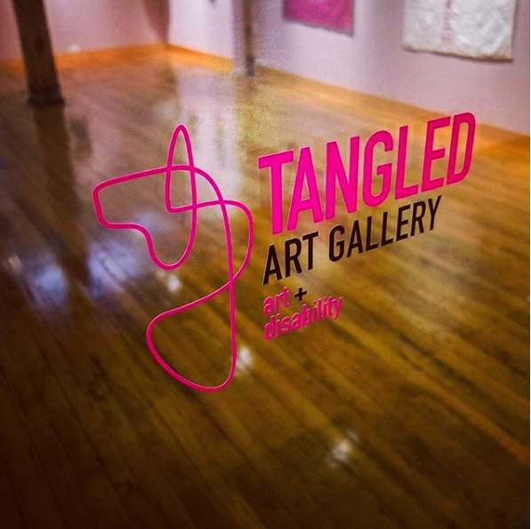 "Image is a photograph of the gallery logo and name ""Tangled Art Gallery art + disability"" pasted on the glass doors of the gallery. Seen beyond the logo is the actual gallery space showing an open space, as well as art hung on the wall at a lower height than what is seen in most other galleries. This is done to accommodate people in a seated position."