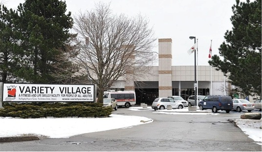 "This image is of a photograph that shows the exterior of the Variety Village building during the winter. A sign on the left-hand side of the photo reads ""Variety Village A Fitness And Life Skills Facility For People Of All Abilities""."
